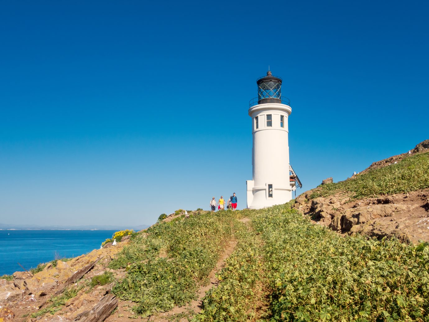People hike at the lighthouse on Anacapa Island in Channel Islands National Park, California, USA on a sunny day.
