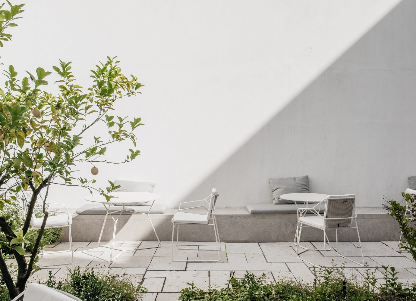 Outdoor seating on the patio with a hard shadow taking over half of the image