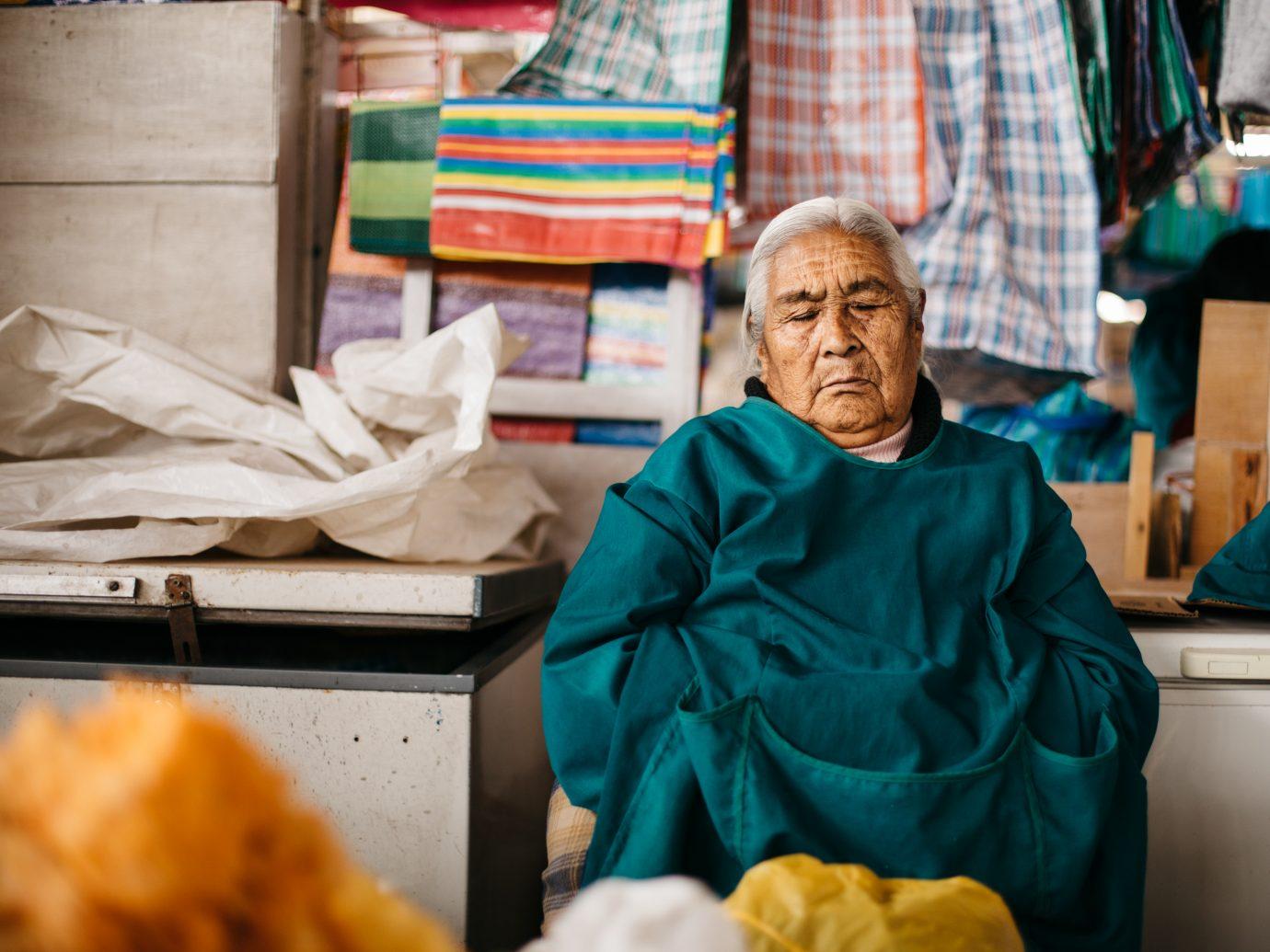 Peruvian man in emerald green outerwear resting