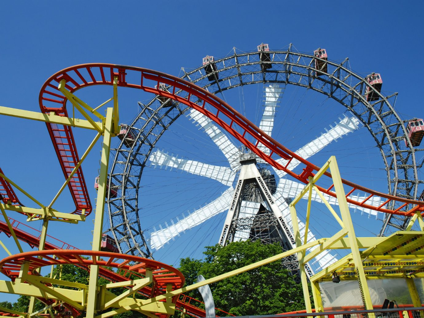 view of rollercoaster and ferris wheel in Prater park in Vienna