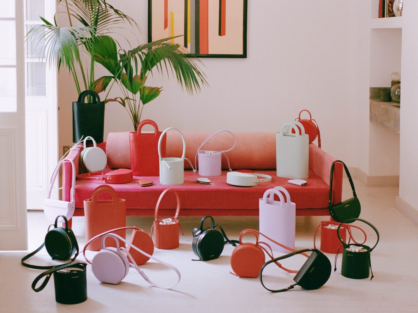 Beautiful assorted leather purses and wallets on a red couch in a white interior space from Audette