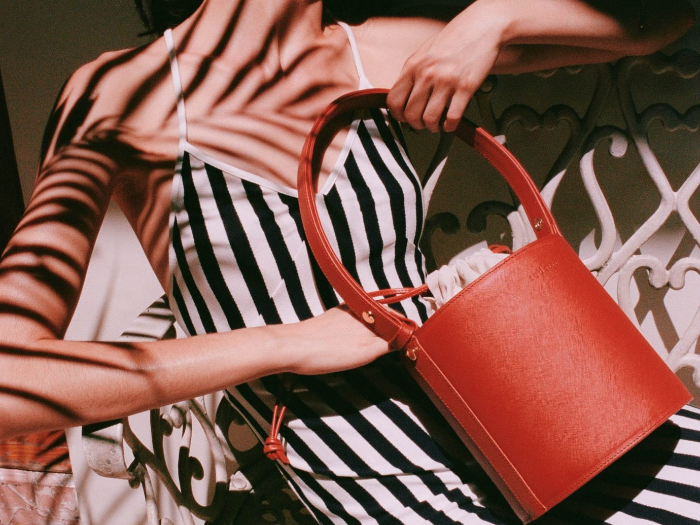 Woman in black and white striped dress holding a red purse with a shadow of a plant on her body