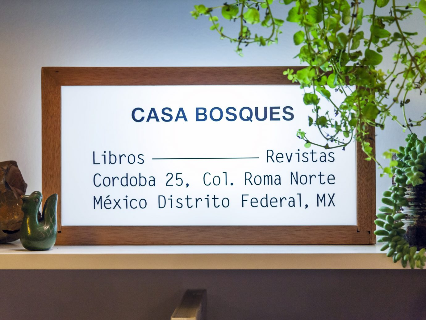 Florescent lit sign listing the location of Casa Bosques