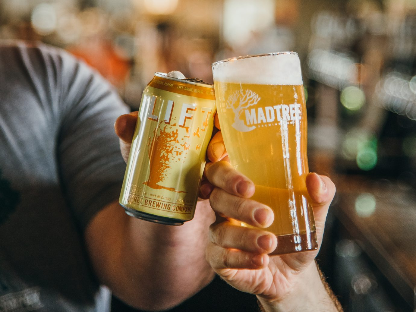 2 friends tapping to a cheers with craft beers at MadTree Brewing