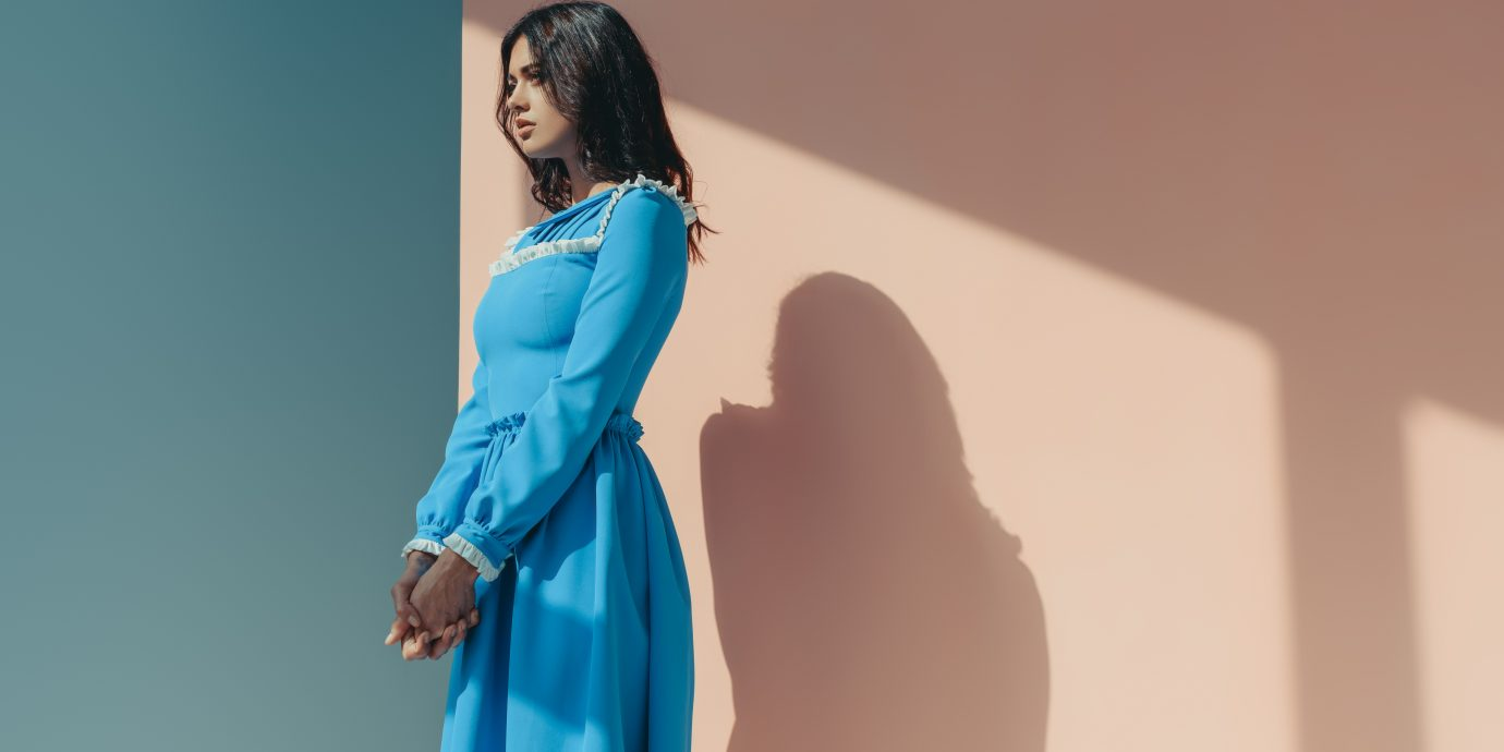 Side view of attractive woman standing in fashionable turquoise dress with long sleeves and looking away