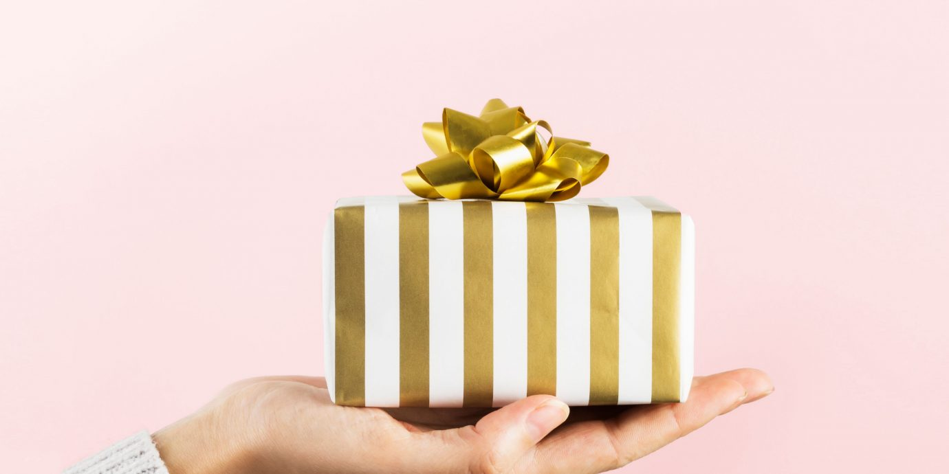 Best Cyber Monday Deals, fold and white striped wrapped gift in someones hand