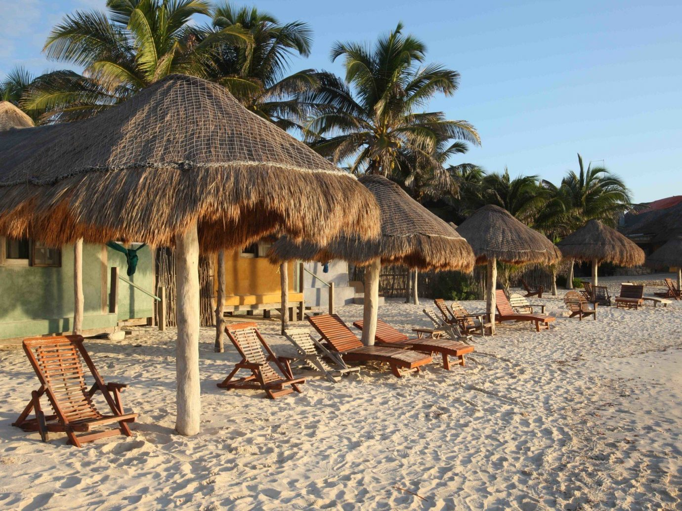 sandy beach and wooden lounge chairs in Tulum
