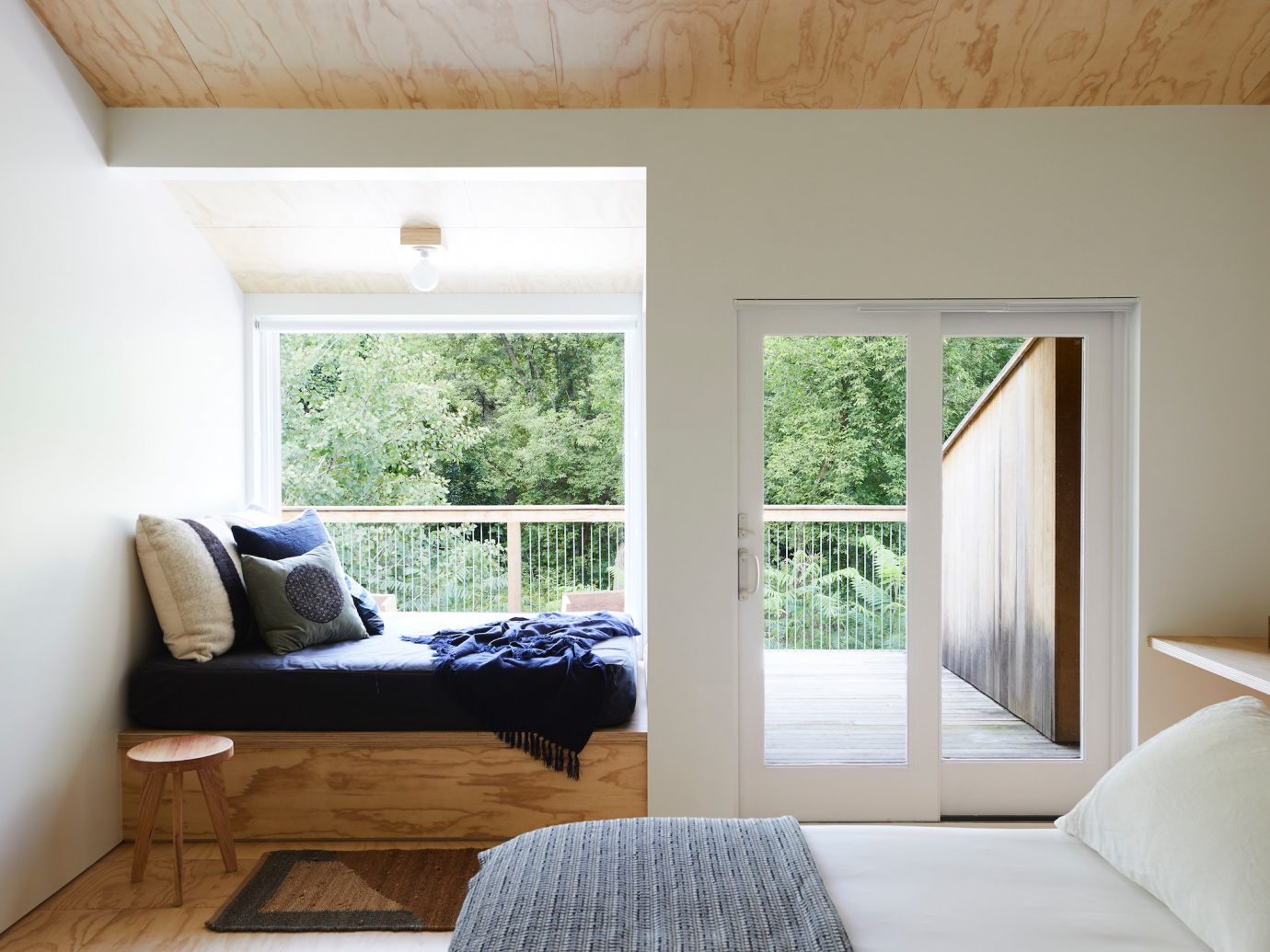 White room with a bed another hangout bed by a window with a view of nature and a private deck