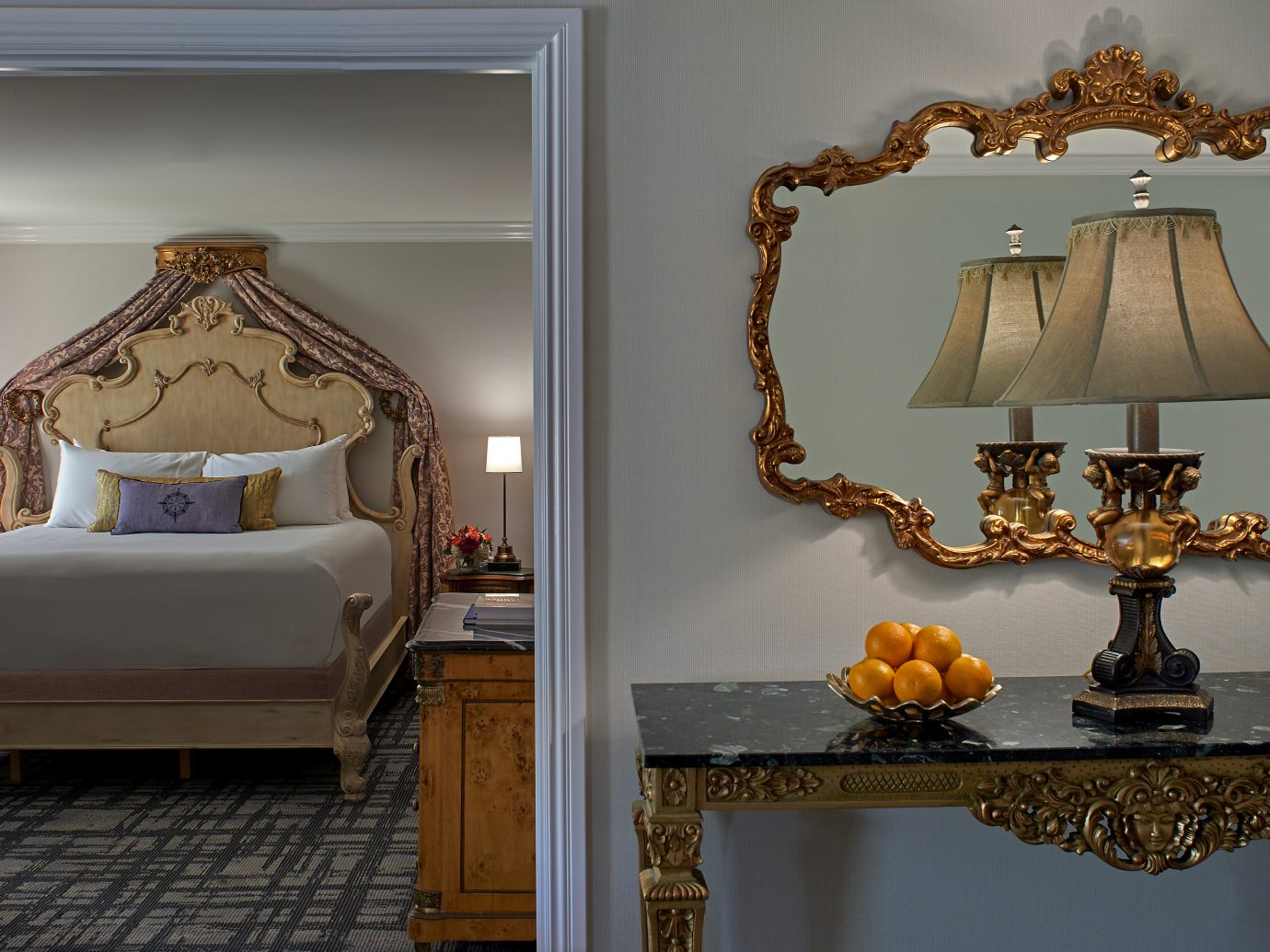 Suite at Hotel Viking showing a mirror and table in the outer room and a queen size bed inside the room