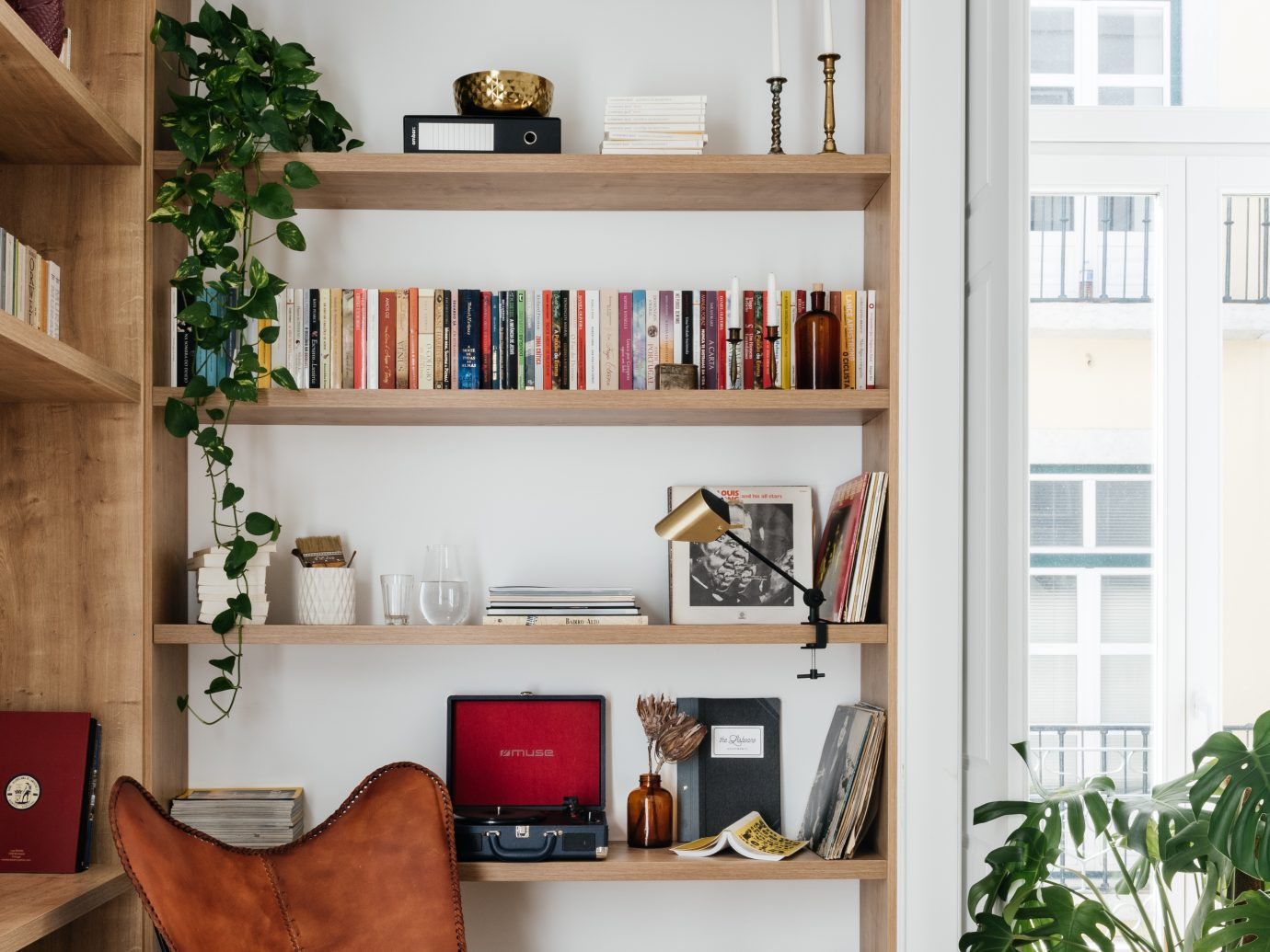 Spacious book shelving with house plants and an antique, trendy chair