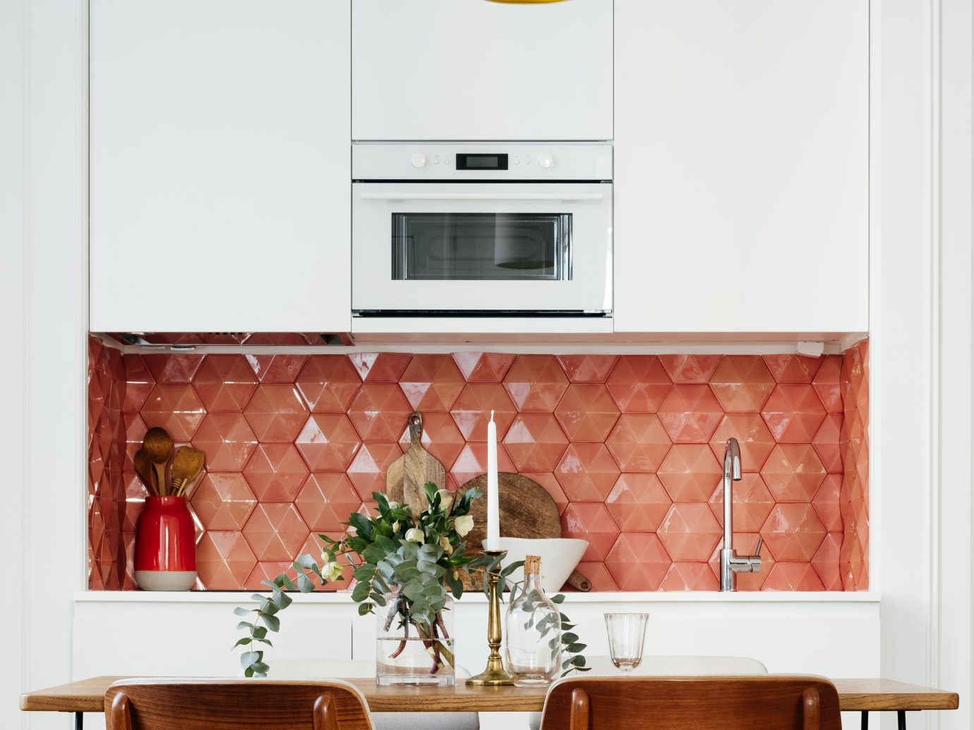Kitchen space with house plant on table and salmon wall tiling