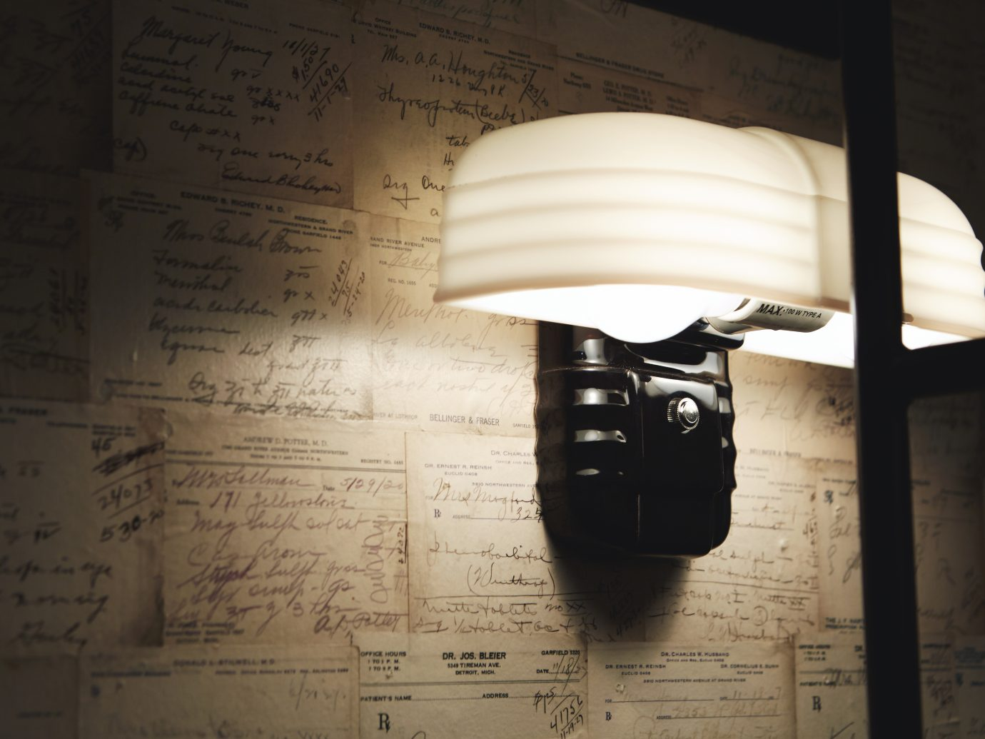 """Sundry + Vice interior lamp with a wall coveringof actual handwritten prescriptions from the 20's and 30's. We have prescriptions for cocaine, cannabis, opium and host of other """"medicines"""""""