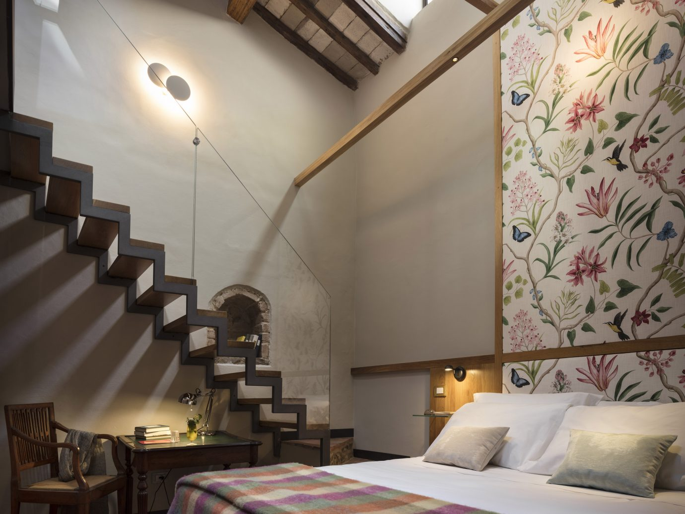 Interior room space at Ottantotto with bed and rail-less stairs leading up