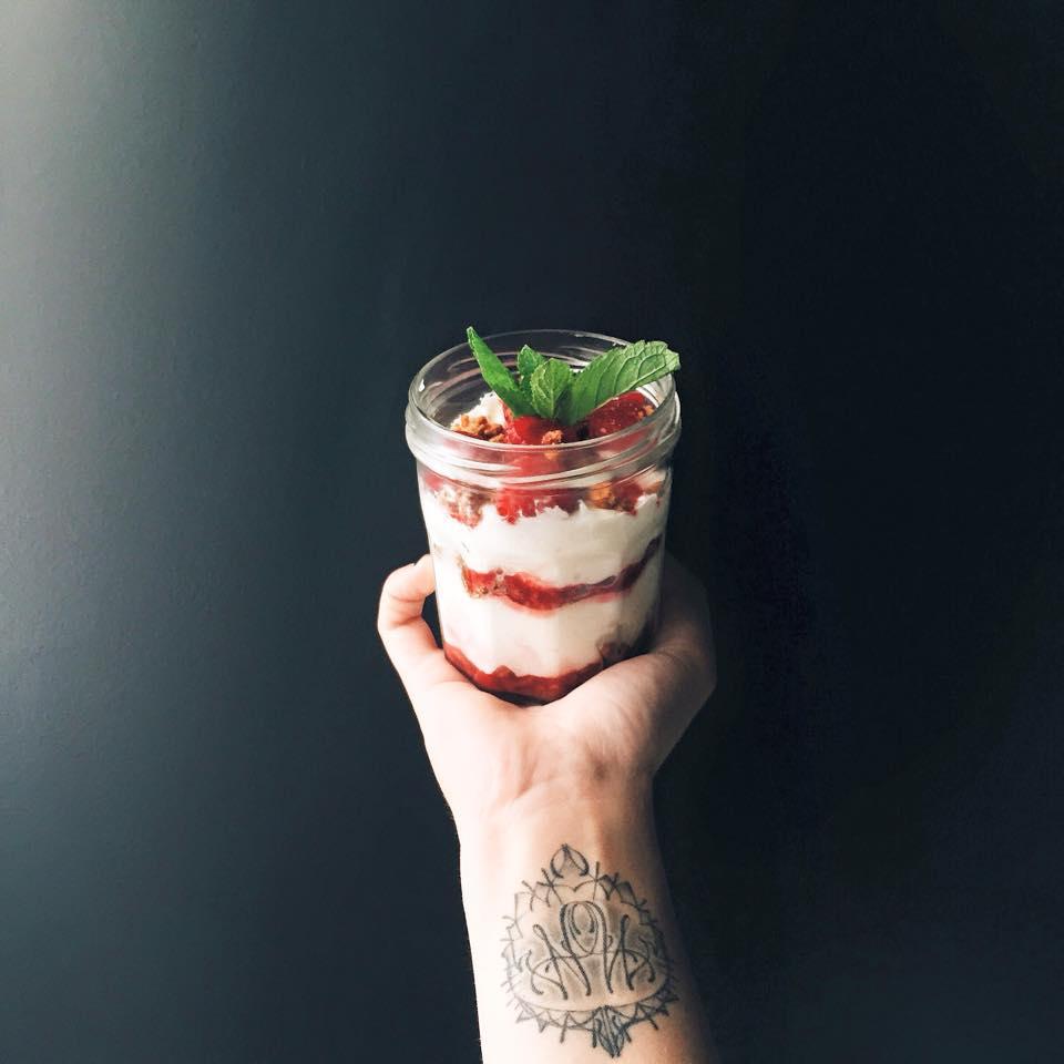Dessert in a jam jar held by someone with a wrist tattoo
