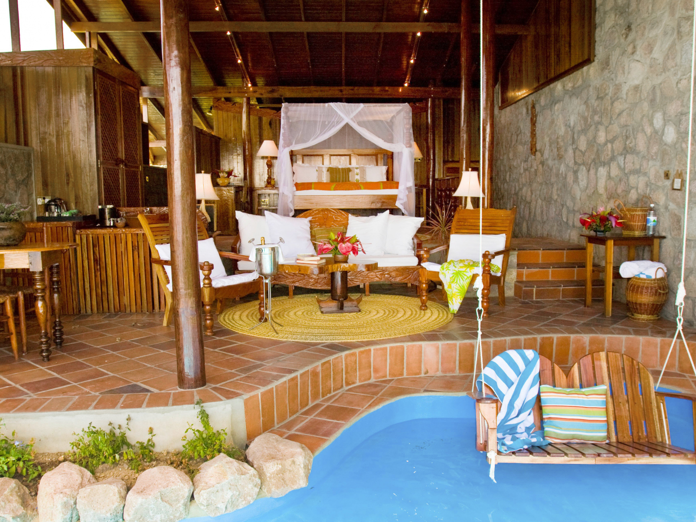 Open air room with swinging bench and water underneath at Ladera Resort