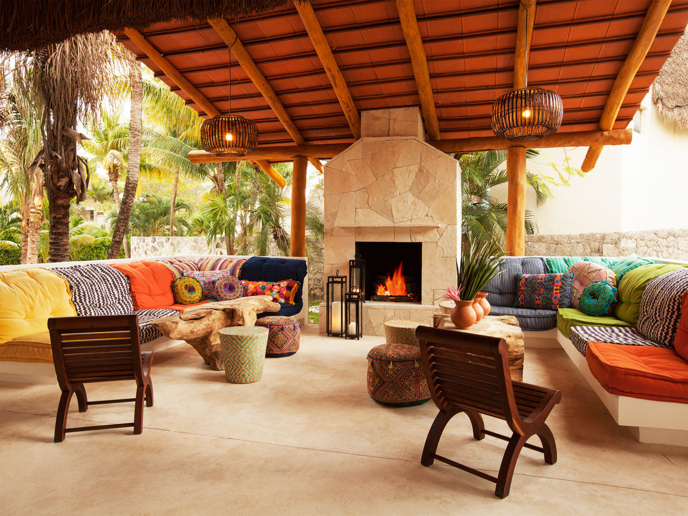 Warm open wall interior with bright colored couches and a fire place at Mahekal Beach Resort