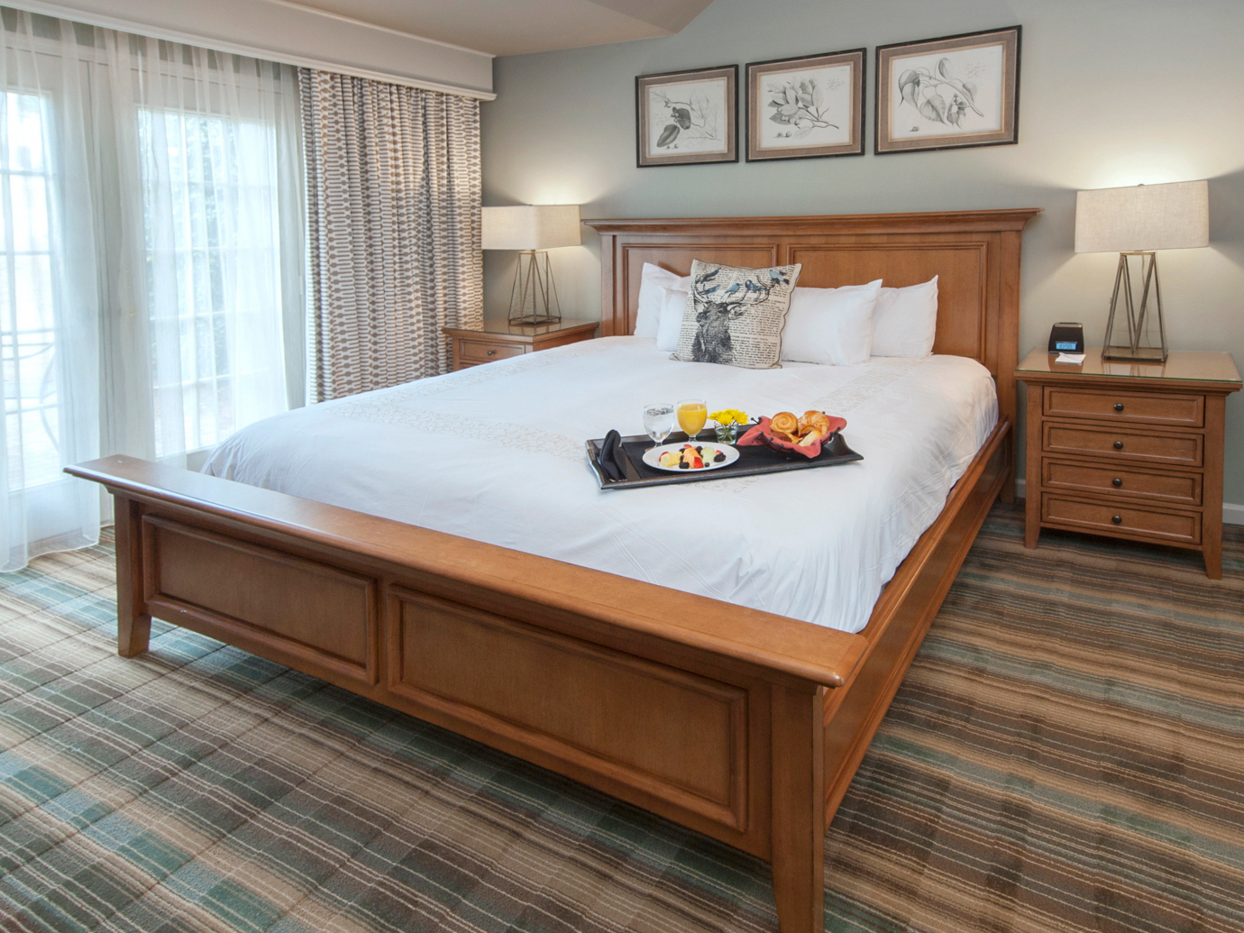 Queen bed with food platter in a suite at Chateau Elan Winery & Resort