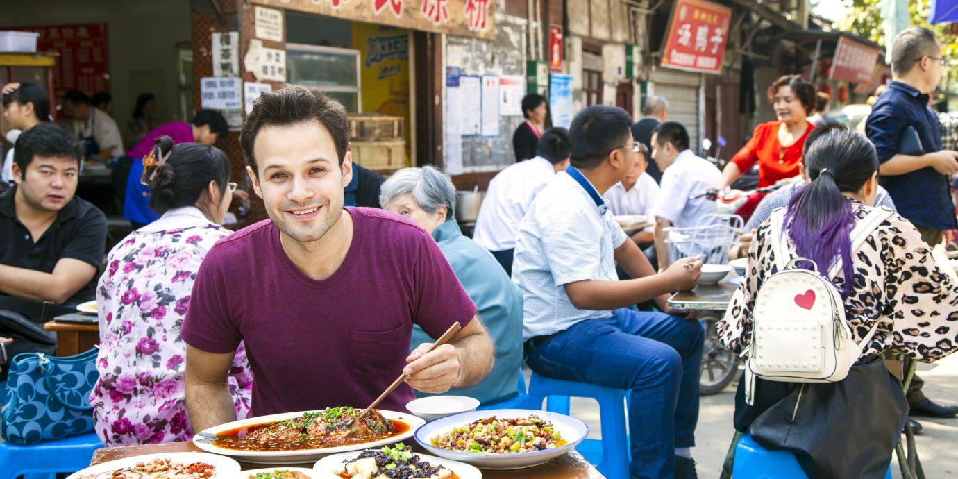Trevor eating food in an asian market