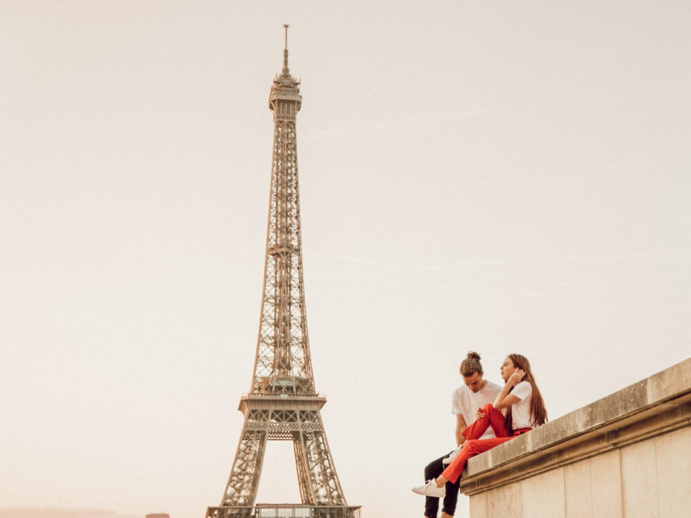 Couple sitting on a building in front of the Eiffel Tower