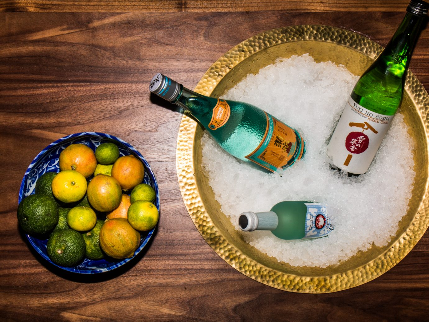 Asian bottles on ice next to limes and lemons