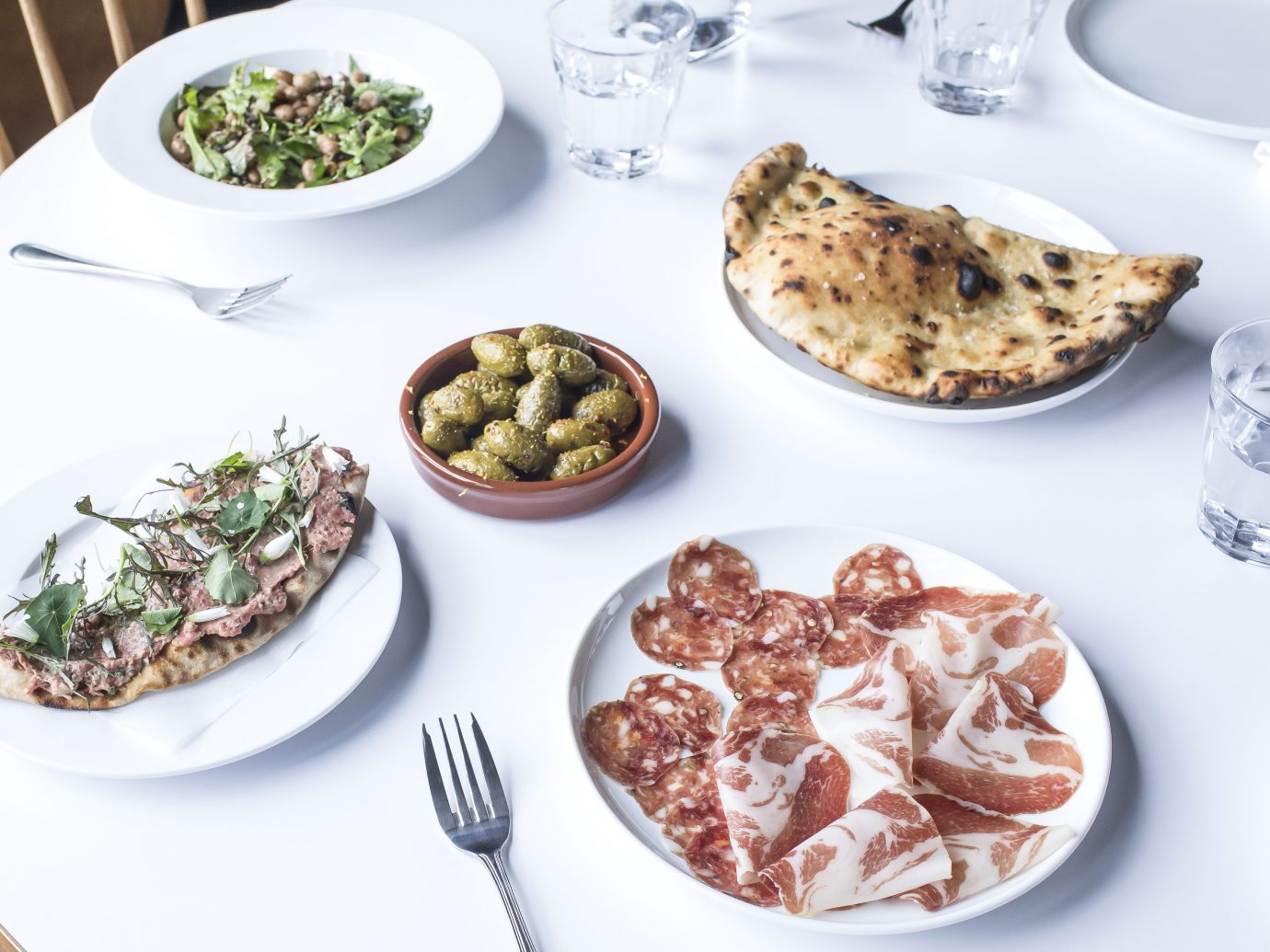 Table of food feature prosciutto, olives, pizzas, and salad
