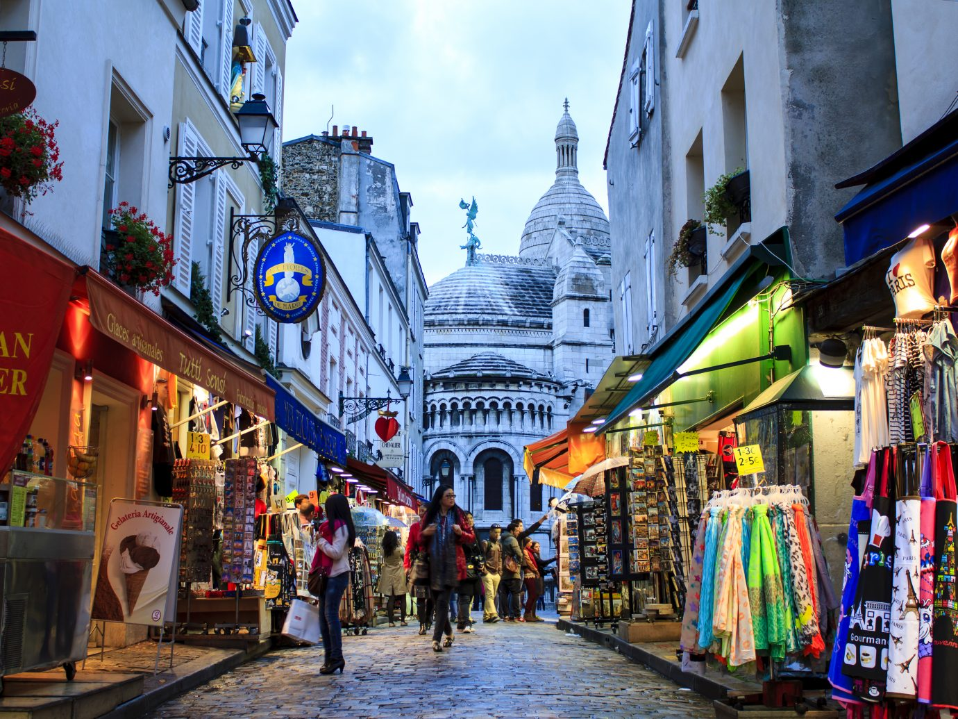 """Montmartre by twilight - tourists and Parisians walking around shopping street near Sacre Coeur."""""""