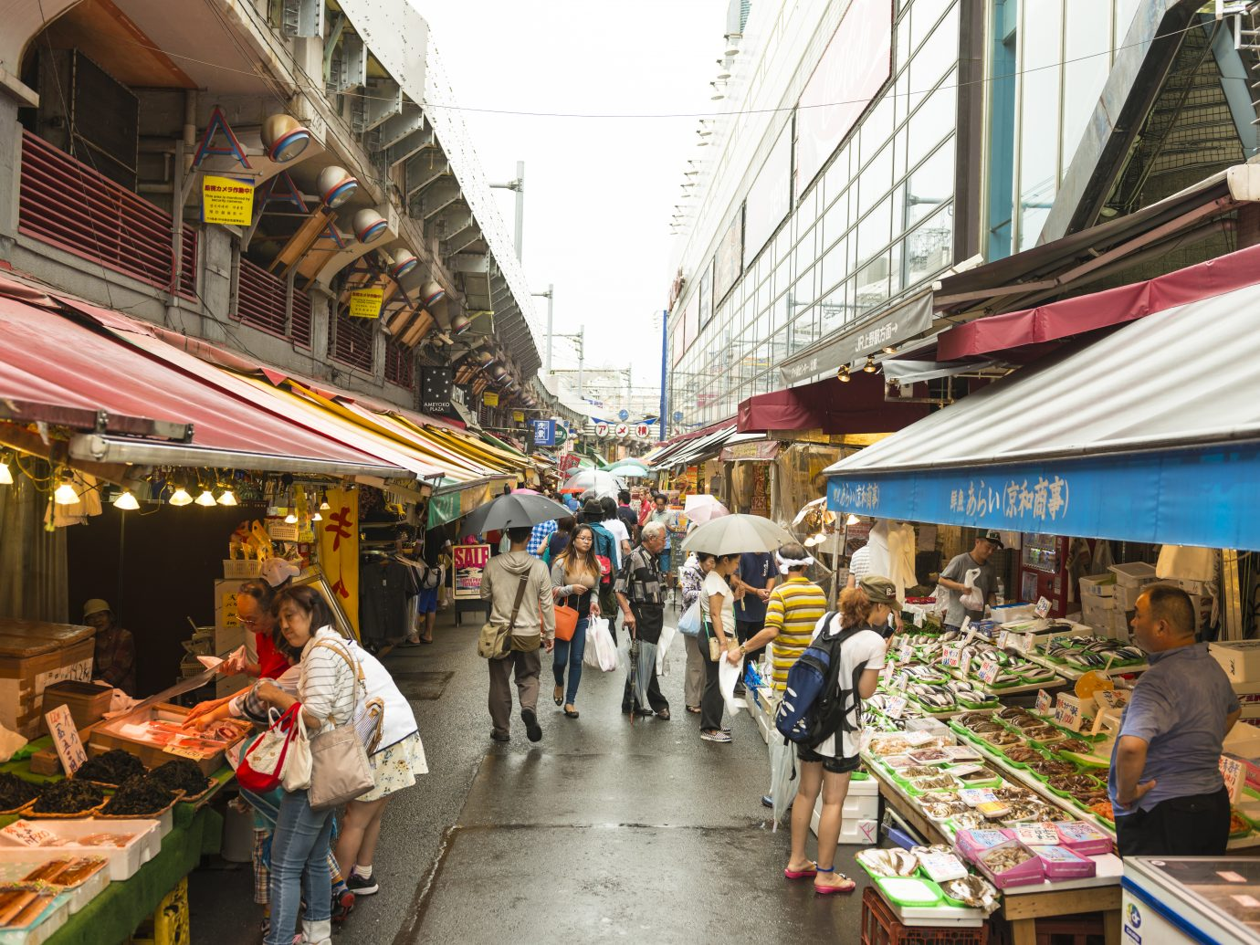 The outer market, fish stalls and many people, some with umbrellas on rainy day buying fish and other seafood.