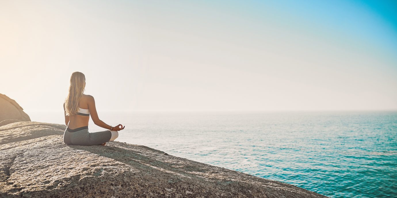 Woman meditating by the ocean, Gifts for the Wellness Guru