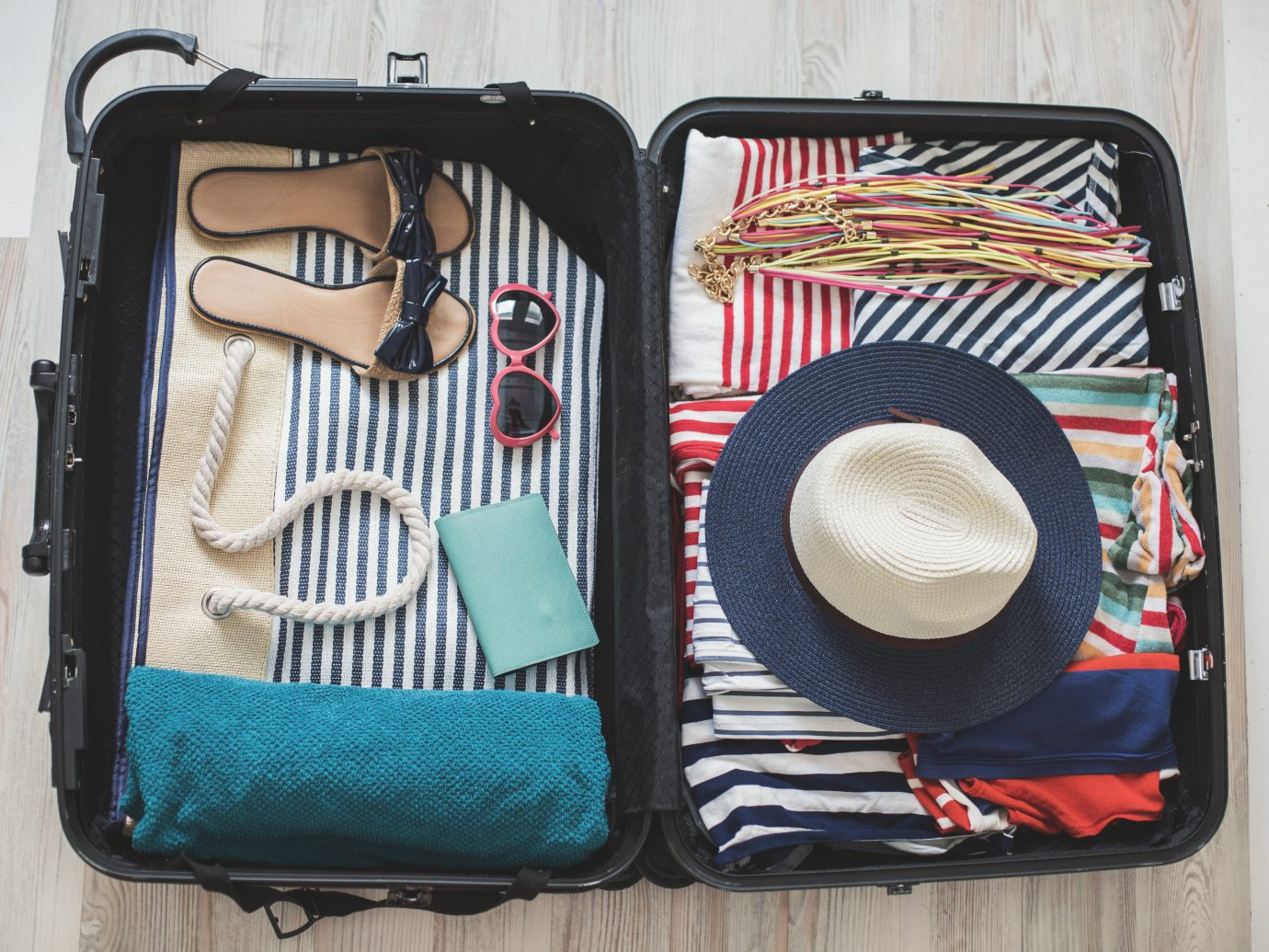 High angle view of summer clothes, slippers, sun hat, sun glasses, beach towel, and other accessories arranged in a suitcase.