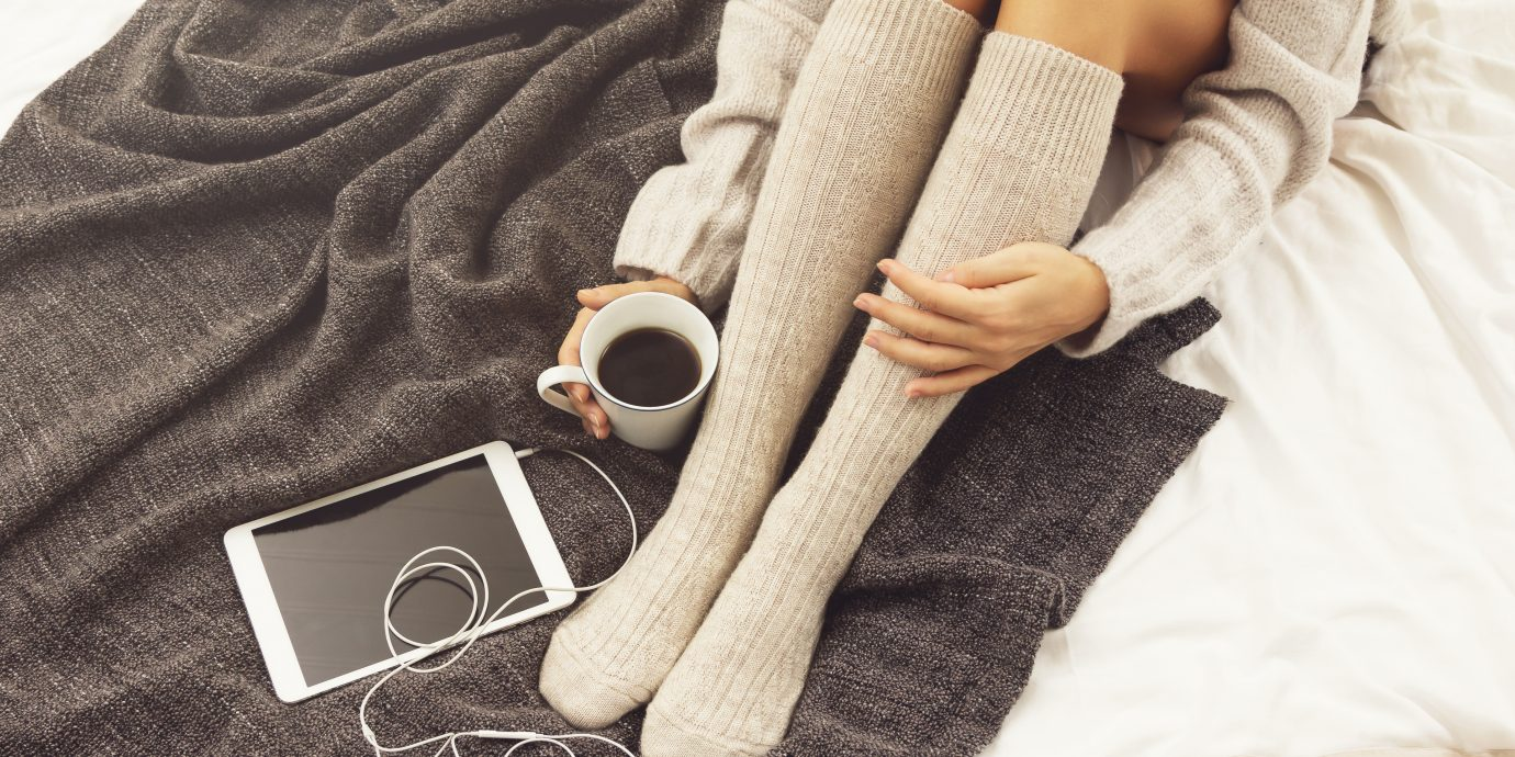 Woman in warm woolen stockings is drinking hot coffee at cold winter day