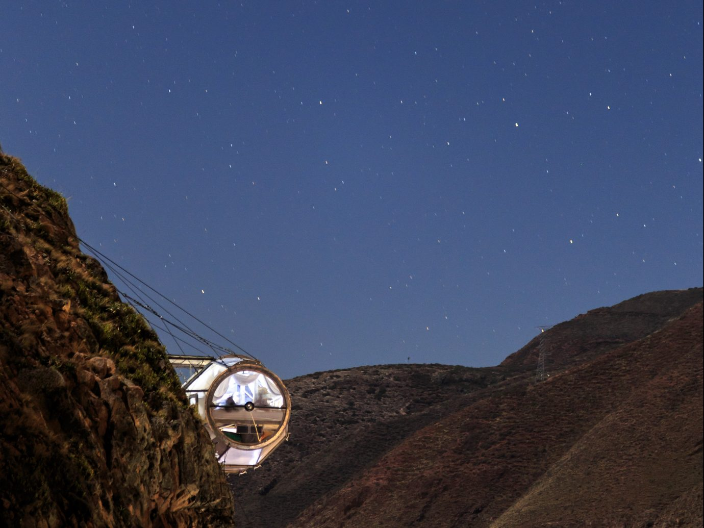Hanging pod hotel room on side of mountain at night