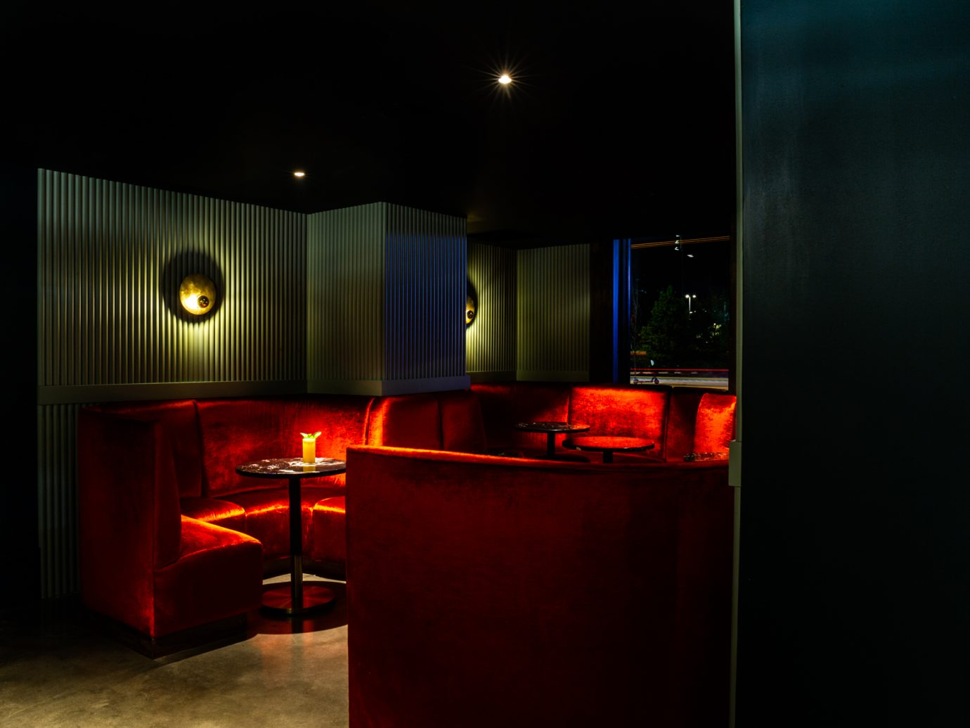 Dim lit lounge area with half circle red velvet couches