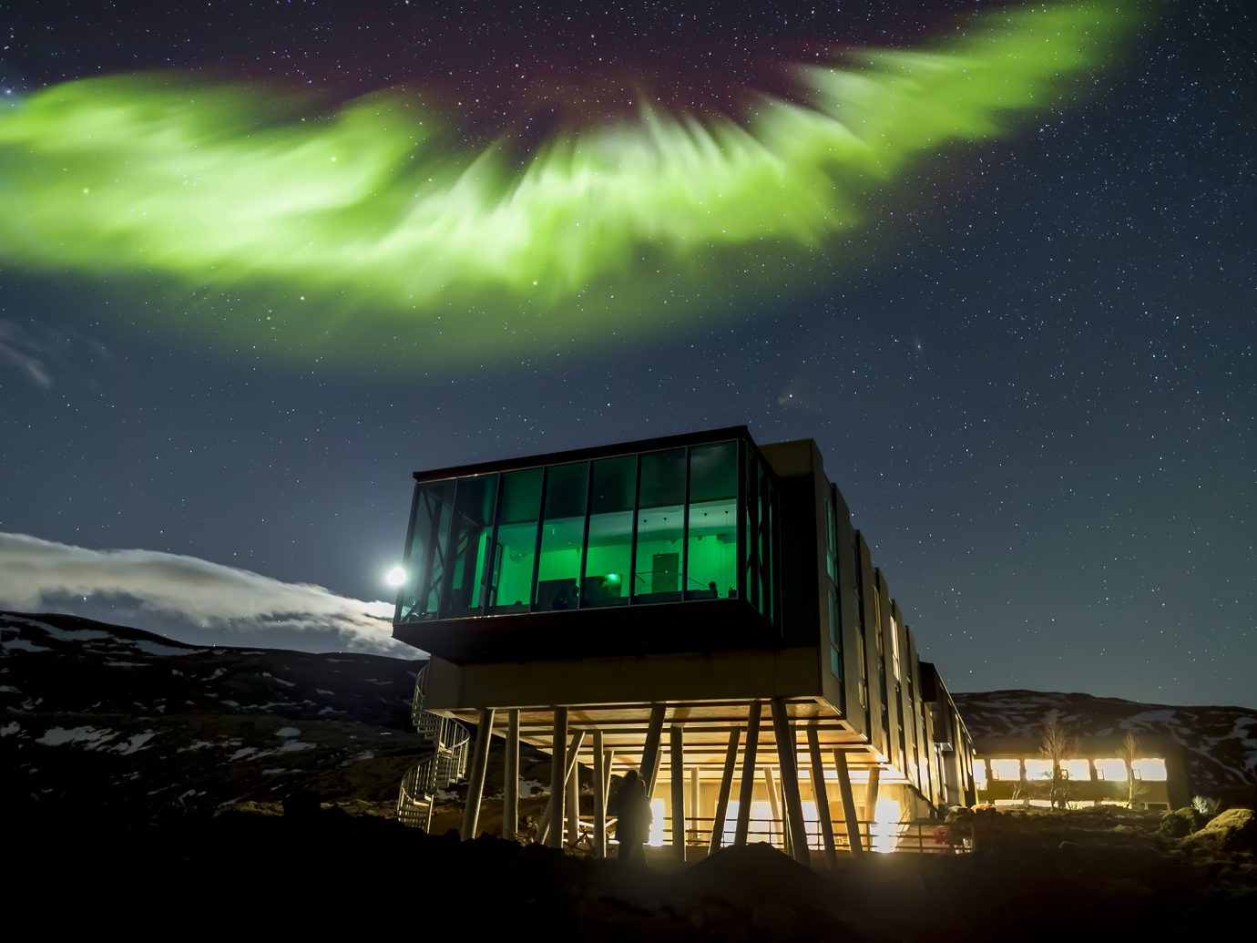 Exterior of ION Adventure Hotel on stilts at night with Northern Lights overhead