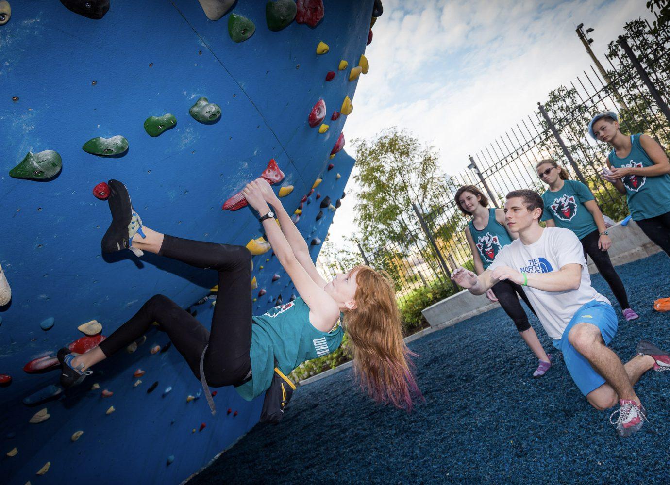 girl hanging on rock climbing wall