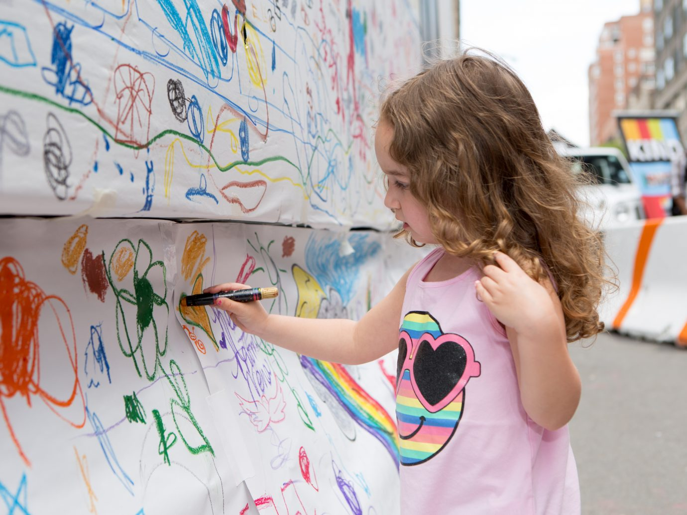 little girl drawing on paper attached to wall