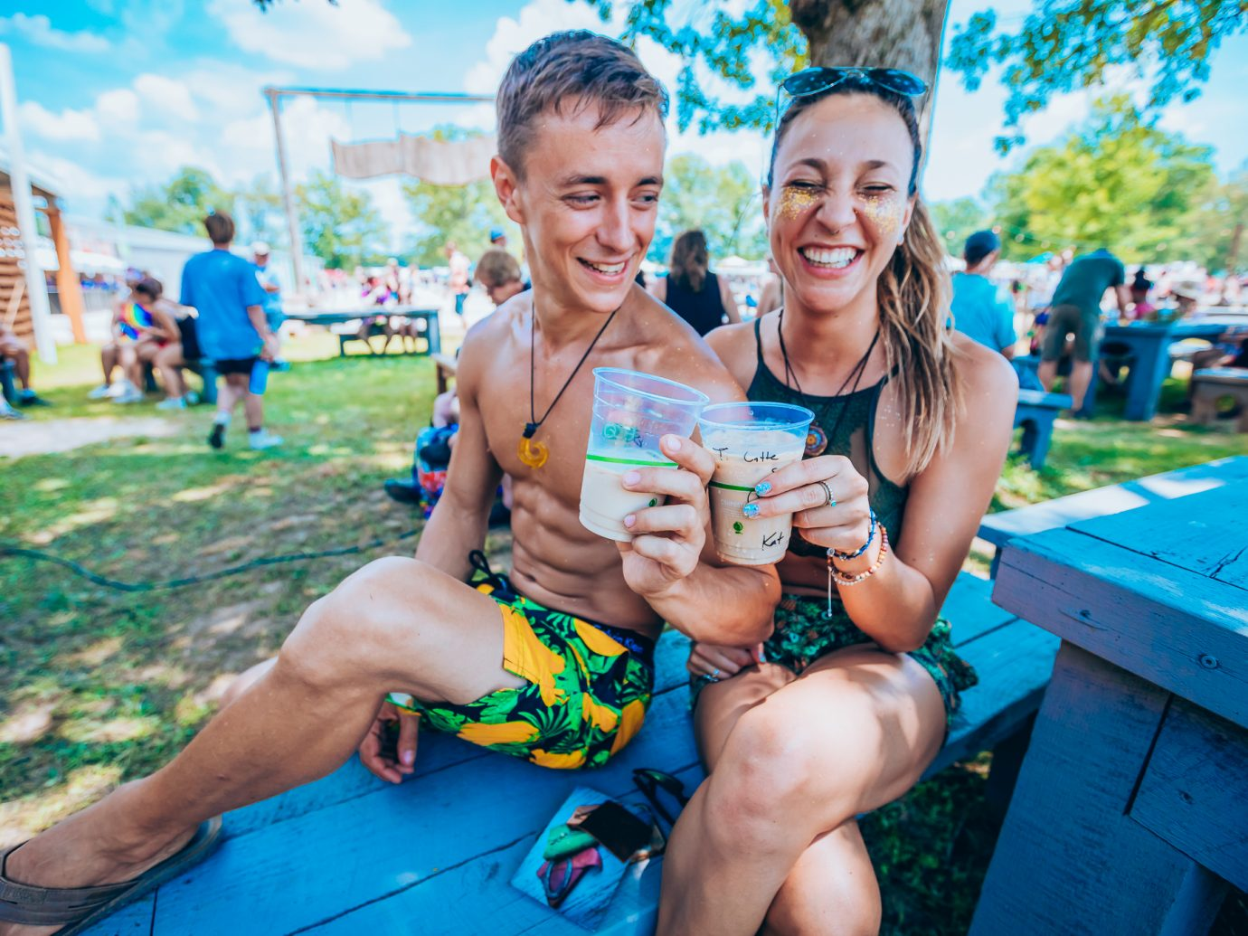 couple cheersing their drinks on a blue picnic table