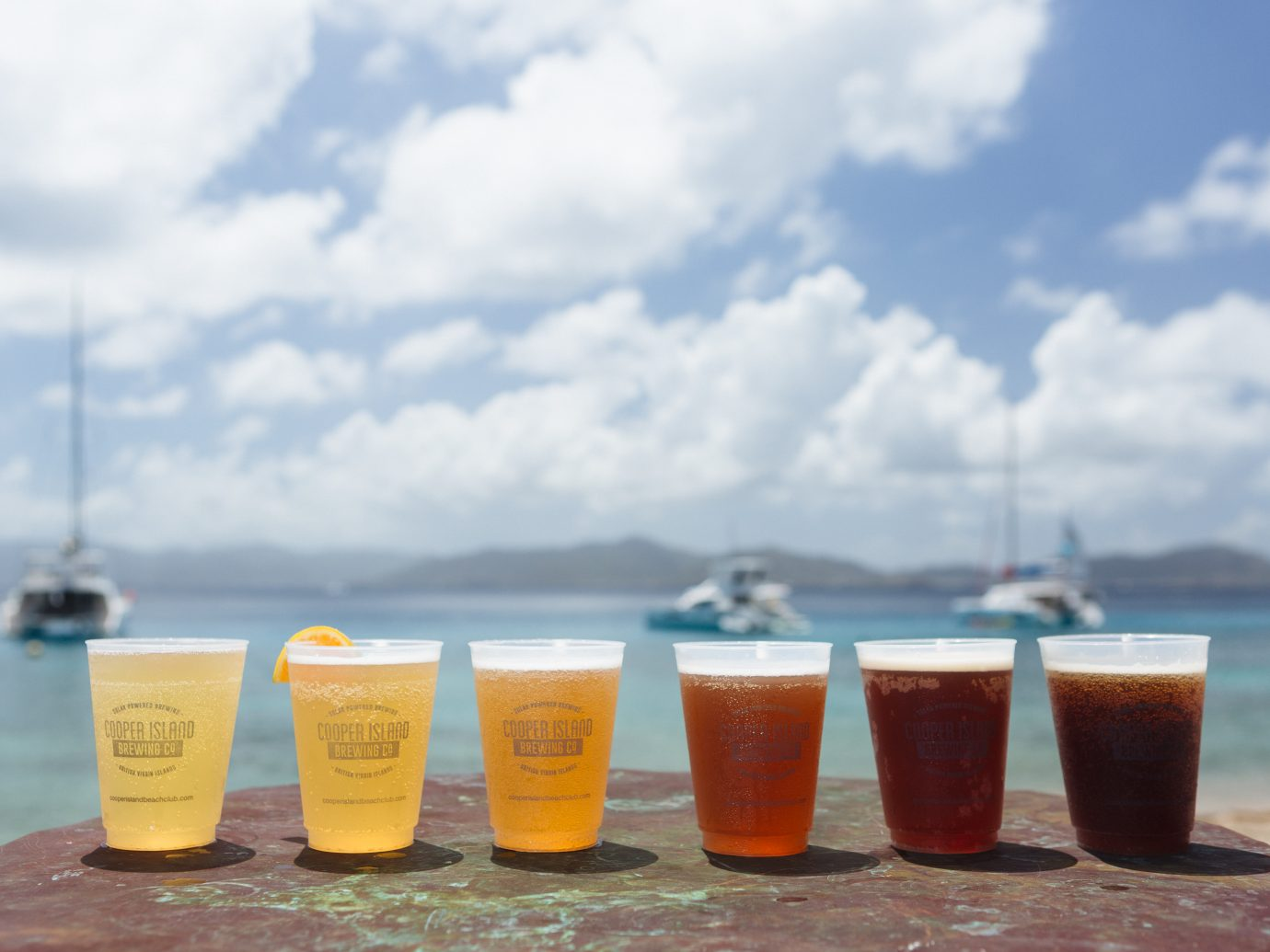 six different beers in a row from lightest to darkest on table with beach in background