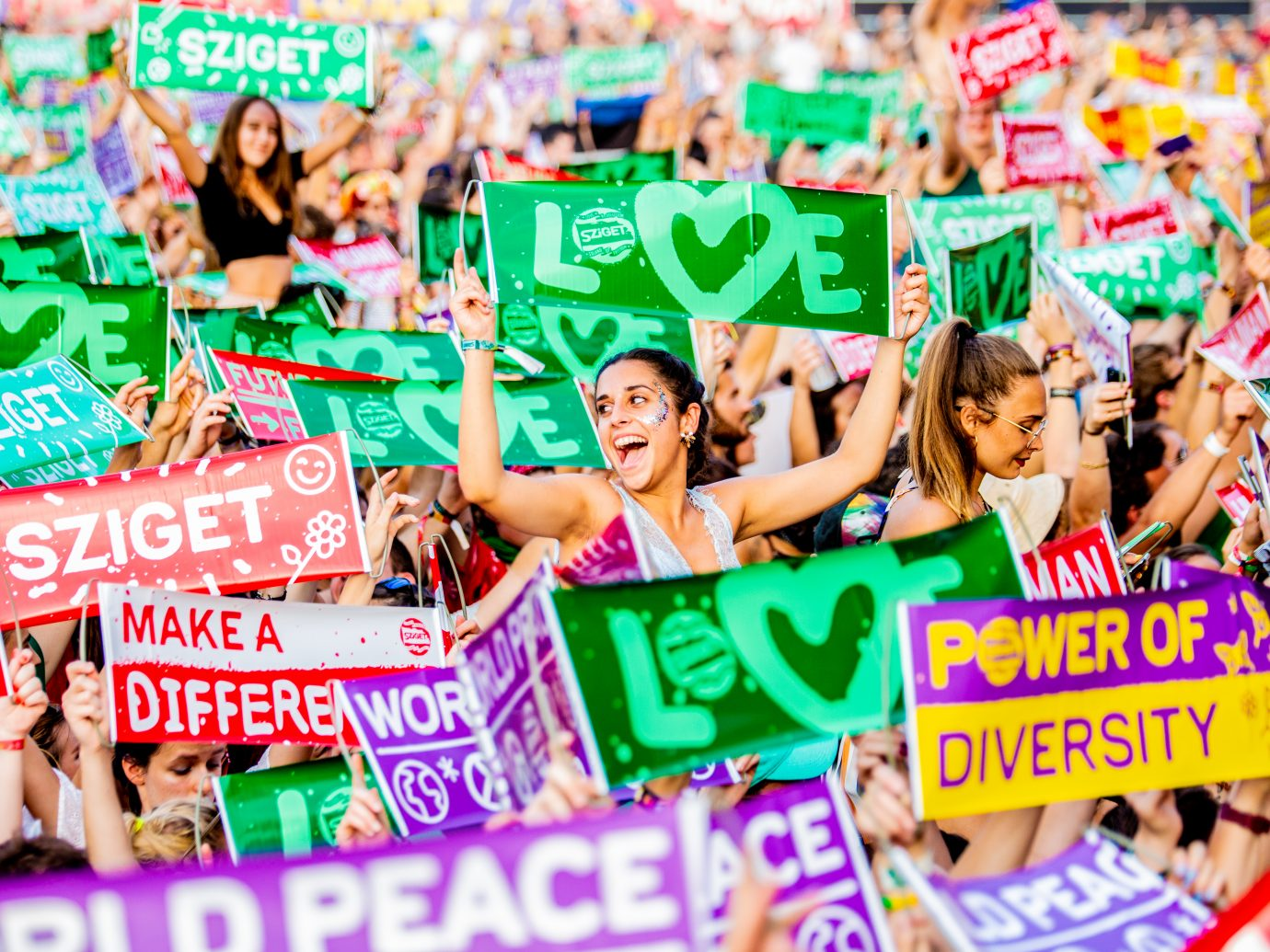 happy people in a crowd at a festival holding signs of peace and positivity