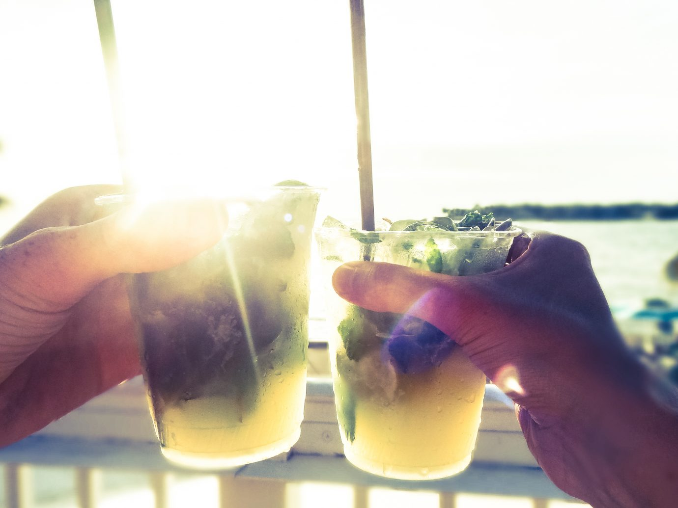 Enjoy the sunset of the Gulf of Mexico while havin' an ice-cold Caipirinha in your hand. I took this picture while drinking on a rooftop bar at the Mallory Square in Key West, Florida.
