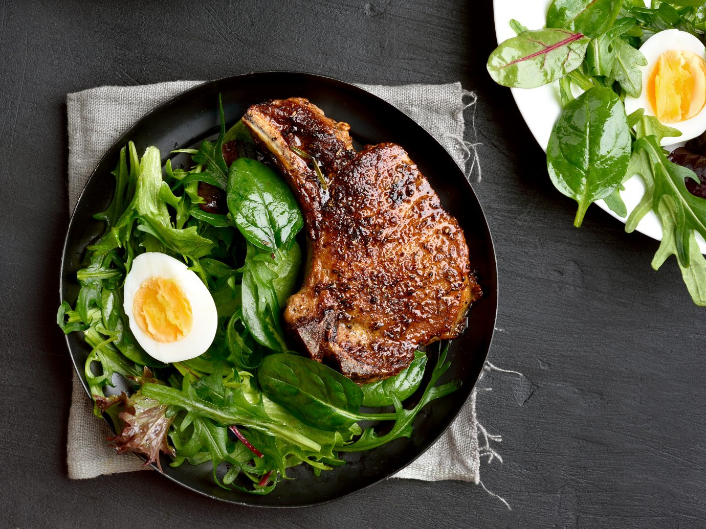 Grilled pork steak with green salad. Top view, flat lay
