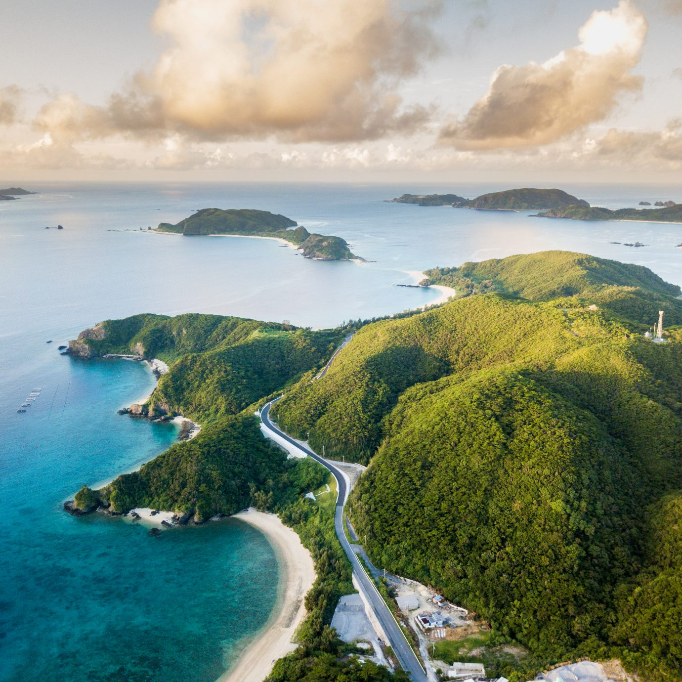 An aerial view over islands with beautiful water and reef surrounding them. From the Kerama island chain in Okinawa, Japan.