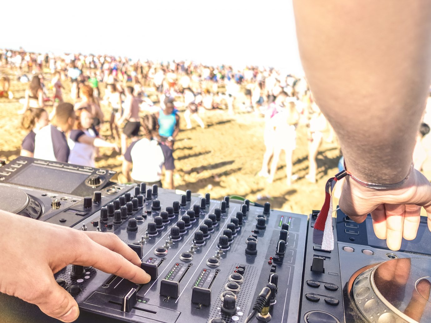 Close up of dj playing electro sound on modern cd usb player at summer beach party - Music festival event and entertainment concept with dancing people - Defocused background with focus on left hand