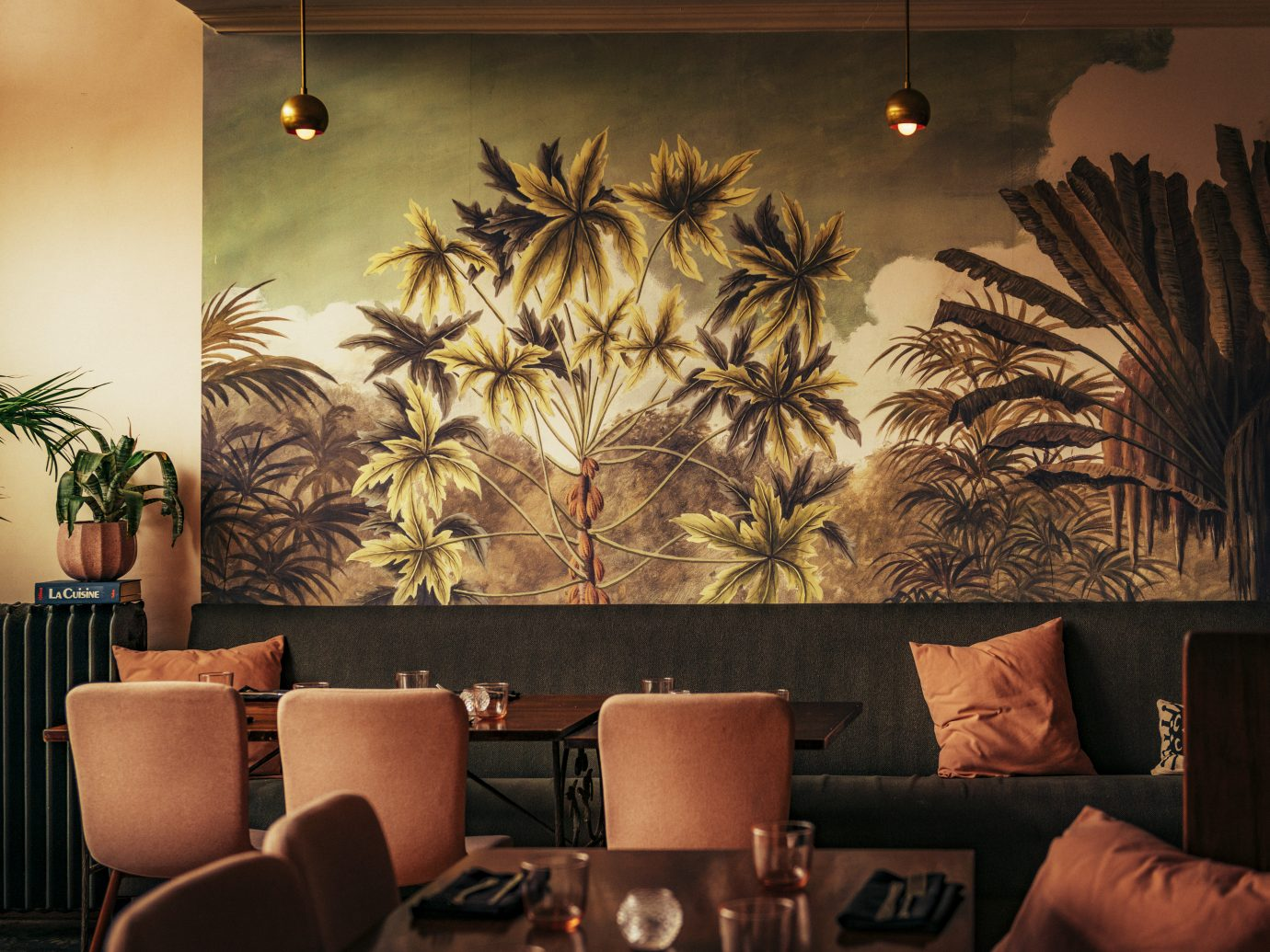 room with tables and a booth with a wall with palm trees