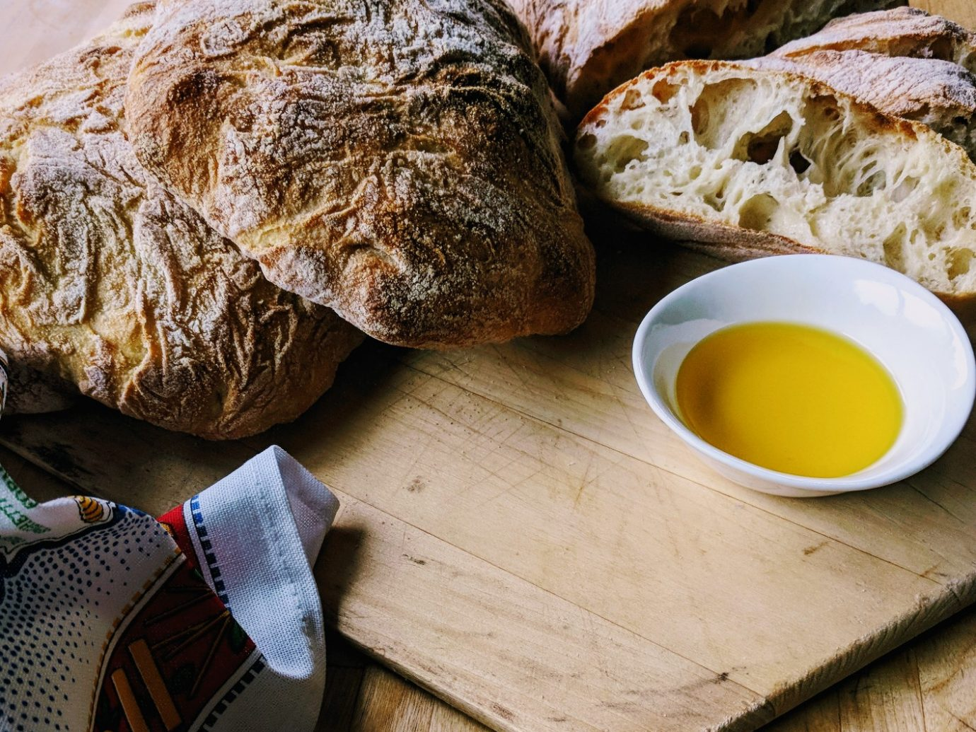 fresh baked bread on a wooden cutting board next to olive oil