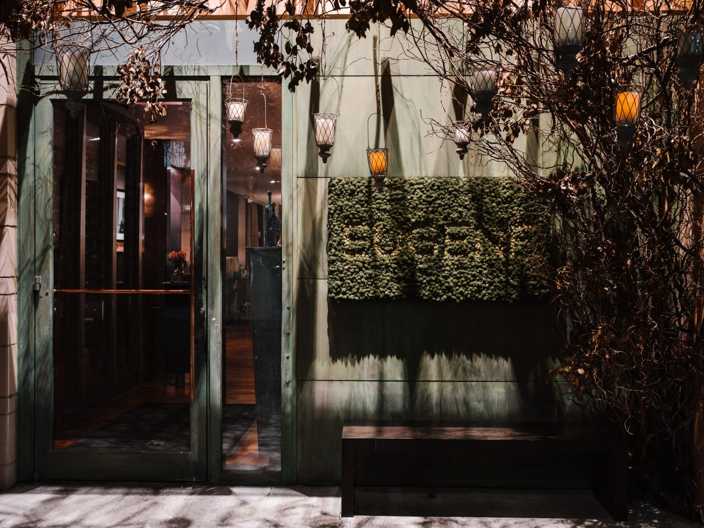 Exterior of Restaurant Eugene with a green plant sign