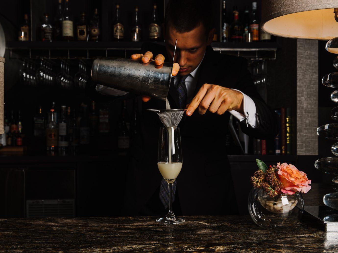 Man straining cocktail in dim lighting