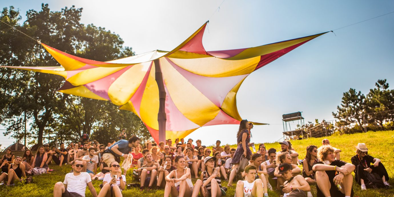 a group of people sitting under a tent in the sun