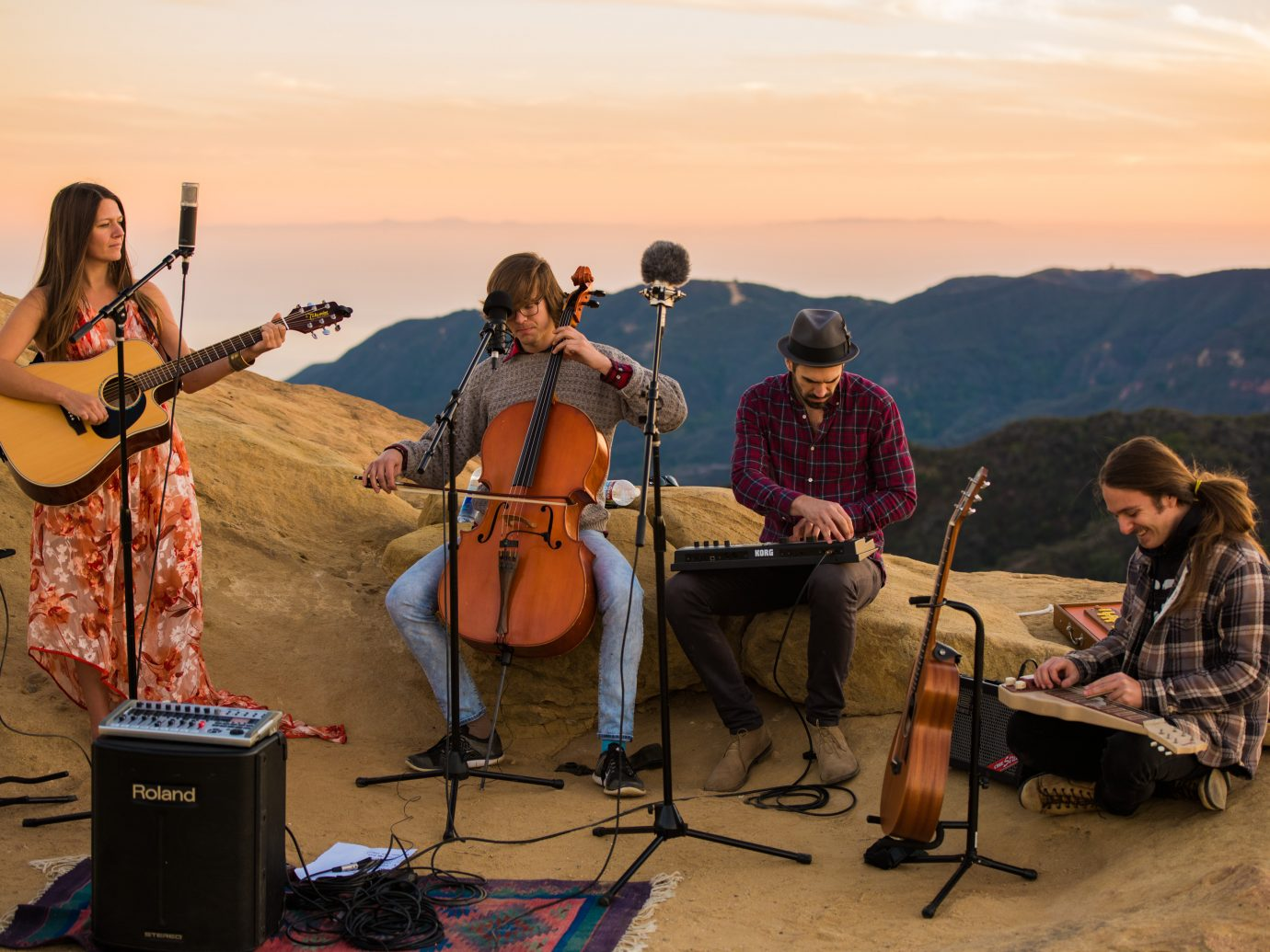 a band performing during sunset on mountains
