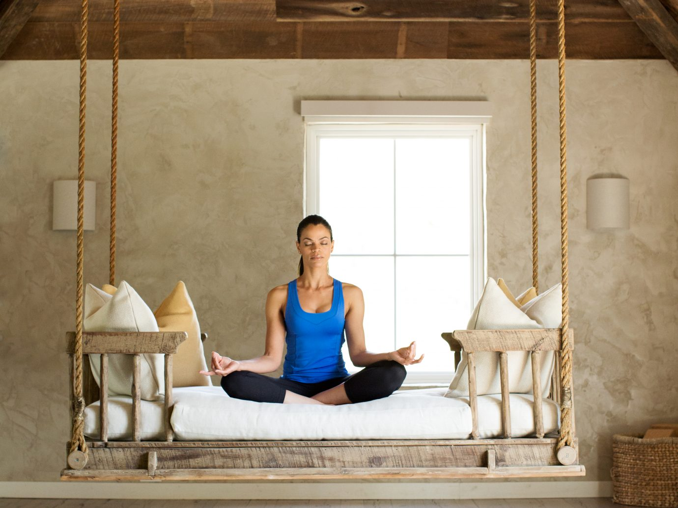 woman meditating on hanging bench