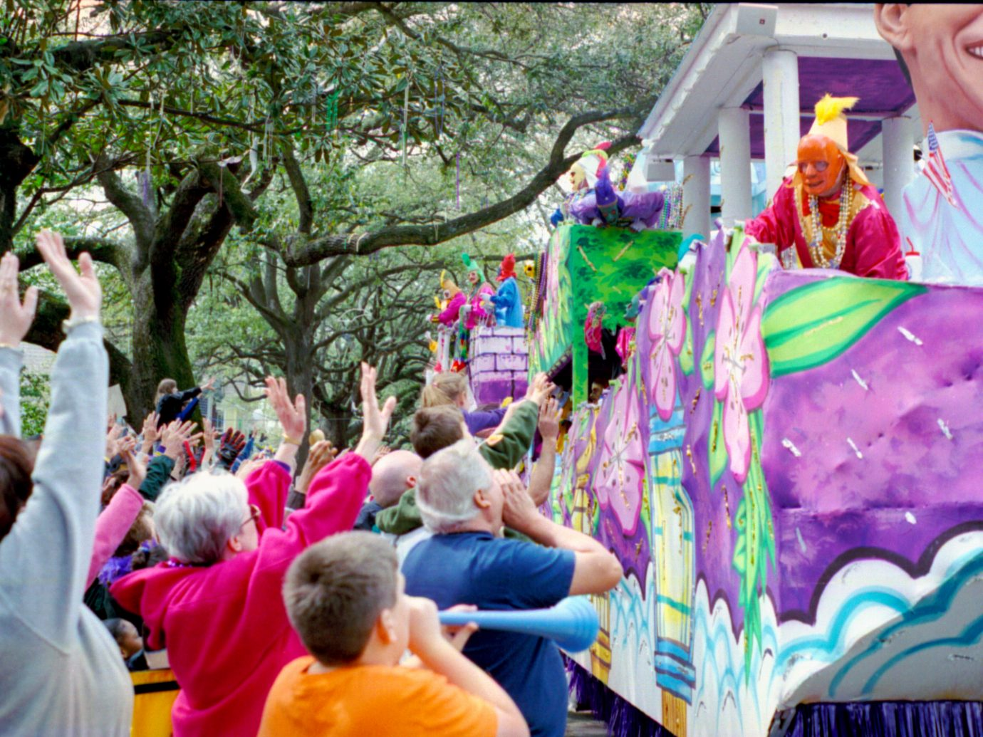 """Mardi Gras Parade on St. Charles Ave - New Orleans. The crowd yells """"throw me something mister"""" at the Krewe."""